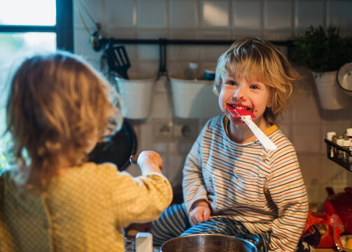 Small boy and girl indoors in kitchen at home, helping with cooking.