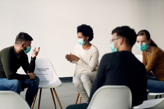 Group of people wearing protective face masks while talking during psychotherapy meeting.