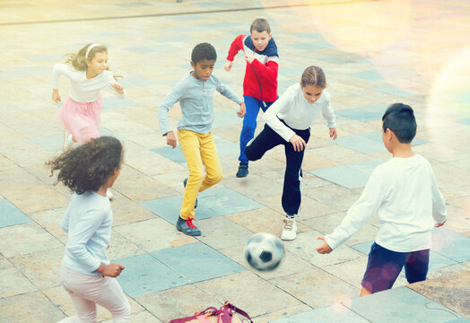 International group of sports tweenagers having fun together outdoors, playing football in school yard after lessons on autumn day.
