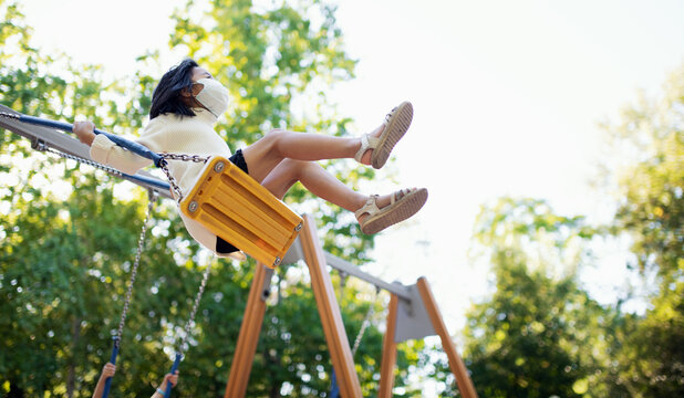 Small girl with face mask on swing outdoors in town, coronavirus concept.