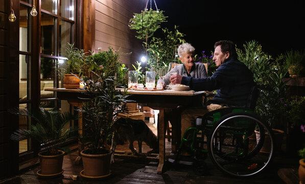 Senior couple in wheelchair having dinner in the evening on terrace, drinking wine.