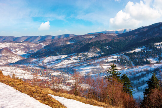 mountainous countryside on a sunny day. late winter scenery or beginning of spring. melting snow and leafless trees on the hills. village in the distant valley. transcarpathia, ukraine