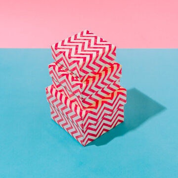 Stack of bright striped gift boxes on a blue and pink pastel background with shadows. Concept of a holiday, Christmas, new year or birthday.