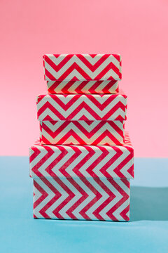 Bright striped gift boxes on a blue and pink pastel background. Concept of a holiday, Christmas, new year or birthday. Close up, pop art, still life.