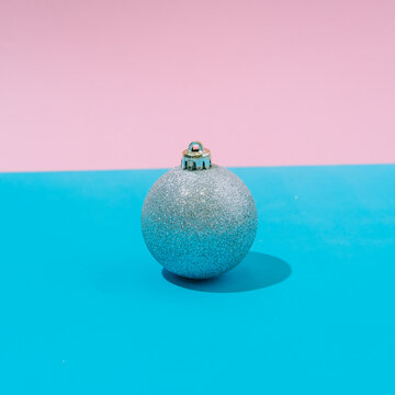 Abstract pastel colorful pink and blue backdrop with silver Christmas ball. New Year Party and Christmas aesthetic.