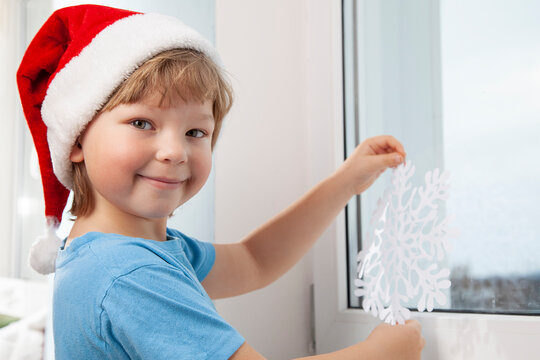 boy is sticking a snowflake winter window in the house Christmas Eve holiday tree
