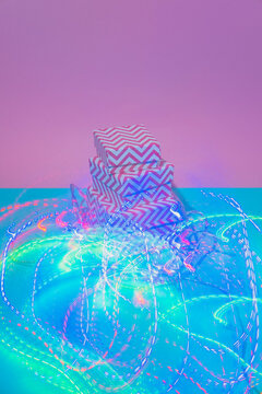 Gift boxes with Christmas lights decoration and long trail. New Year Party aesthetic. Vaporwave holographic light art.