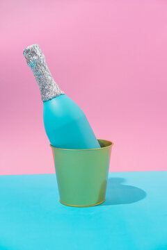 Champagne bottle in ice bucket on abstract pastel colorful pink and blue backdrop. New Year Party and Christmas aesthetic. Pop art, still life