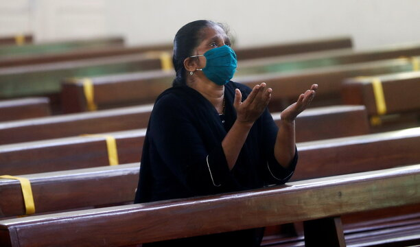 A woman wearing a protective mask prays inside a church after religious places reopened for the public amid the spread of the coronavirus disease (COVID-19) in Mumbai