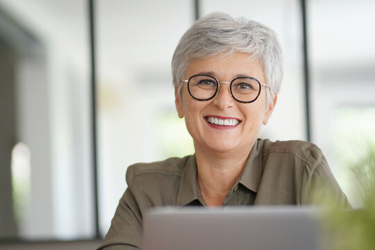 portrait of a beautiful smiling 55 year old woman with white hair