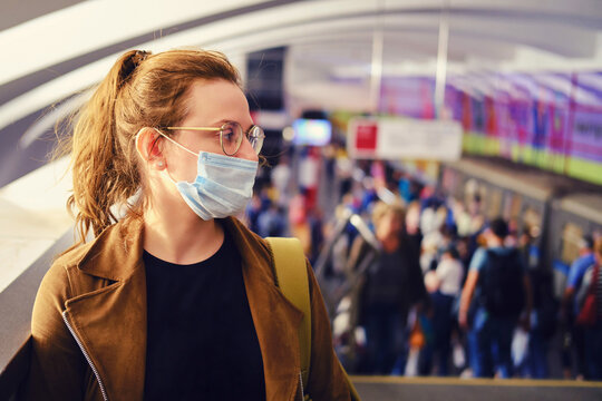 Woman in medical mask stands in the subway against the background of a crowd of people going to the station