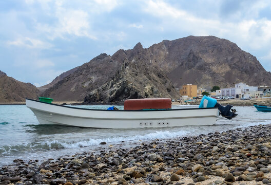 Small docked fishing boat on Darsait Beach, Muscat, Oman. Mountains and fishing village in the background