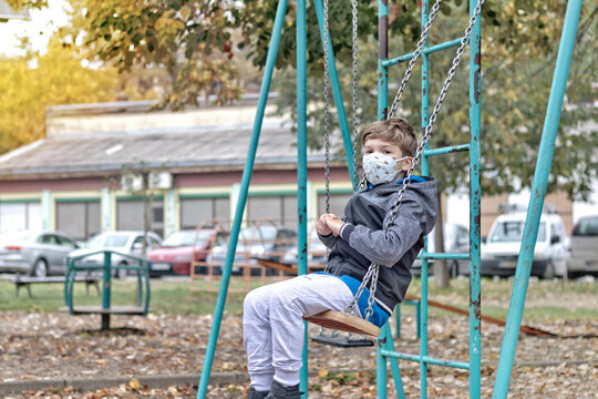 Small boy using a swing while wearing face mask due to COVID-19 pandemic.
