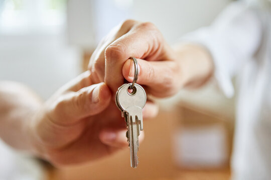 Hands of couple hold keys to new house