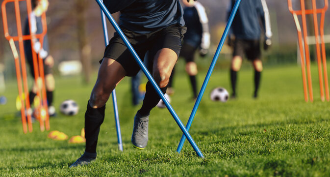 African-American soccer player on training drill. Legs of footballer running on grass practice field. Obstacle course in soccer football. Player running in sports cleats