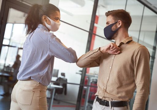 Two young diverse business colleagues wearing face protective masks bumping elbows, greeting each other while working during covid 19 quarantine