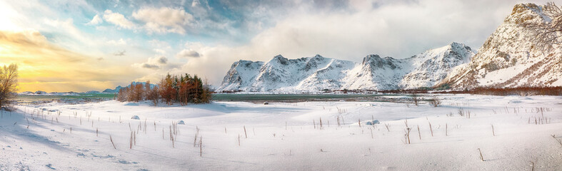 Panoramic winter scenery with frozen fjord on Vestvagoy island at sunset with snowy  mountain peaks near Valberg