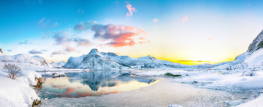 Fantastic frozen Flakstadpollen and Boosen fjords and reflection in water during sunrise with Hustinden mountain on background on Flakstadoya island