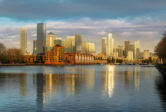 Canary Wharf and South Dock Marina place reflected in the Thames rives in sunset light in London