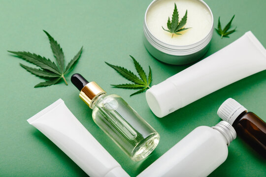 Hemp cbd oil serum in glass dropper bottle with cannabis leaves, Moisturizing cream, Serum, lotion, essential oil. Cannabis leaf with skincare cosmetic product on green background