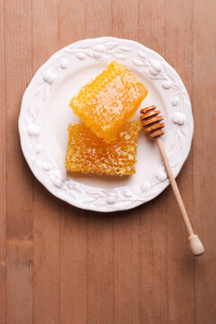 Golden cut honeycomb with a wooden spoon