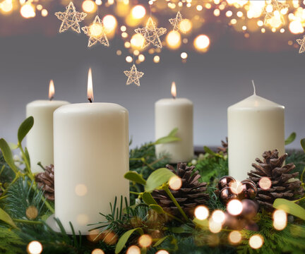 Three burning candle in a advent wreath of fir branches with christmas ornament and golden bokeh. Festive background with short depth of field for the christmas season with space for your text.