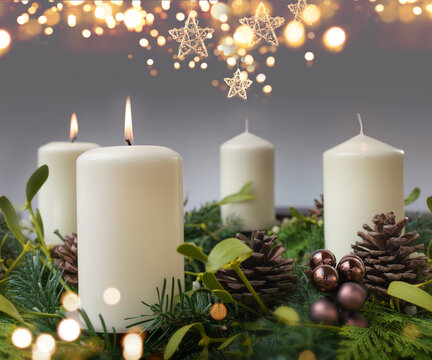 Two burning candle in a advent wreath of fir branches with christmas ornament and golden bokeh. Festive background with short depth of field for the christmas season with space for your text.