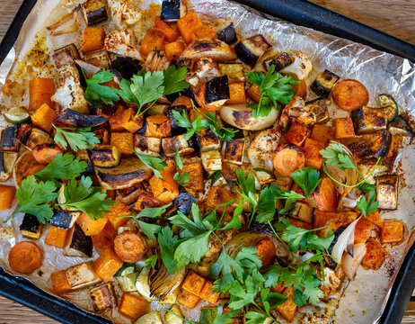 Oven baked  vegetables sprinkled with parsley  on wooden table.