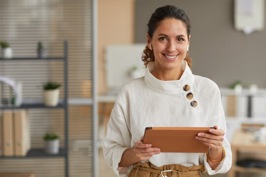 Waist up portrait of elegant modern businesswoman holding tablet and looking at camera with wireless earphones while standing in office, copy space