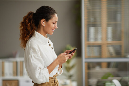 Waist up side view at smiling elegant businesswoman using wireless earphones and holding smartphone while standing at home or in office, copy space