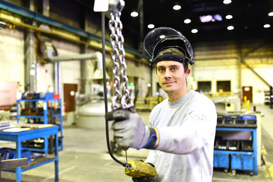 portrait of young smiling industrial worker with helmet in a modern industrial hall at his workplace