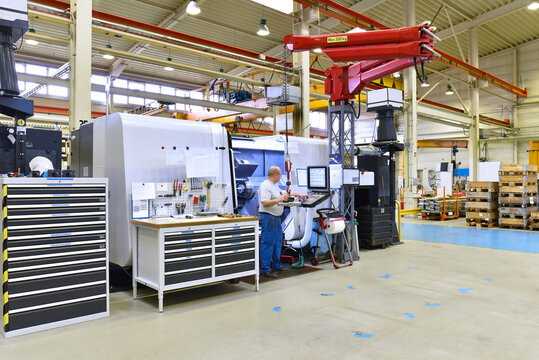 cnc machine in modern industrial mechanical engineering - workers at the workplace