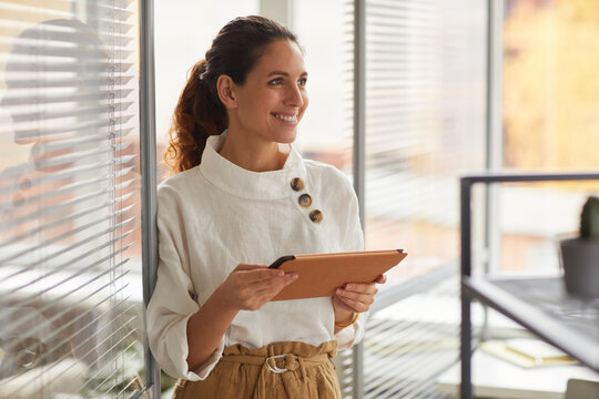 Waist up portrait of smiling successful businesswoman holding digital tablet and looking away while working in office, copy space