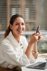 Vertical portrait of smiling elegant woman looking at camera and holding smartphone while enjoying...