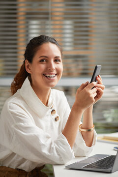 Vertical portrait of smiling elegant woman looking at camera and holding smartphone while enjoying work from home