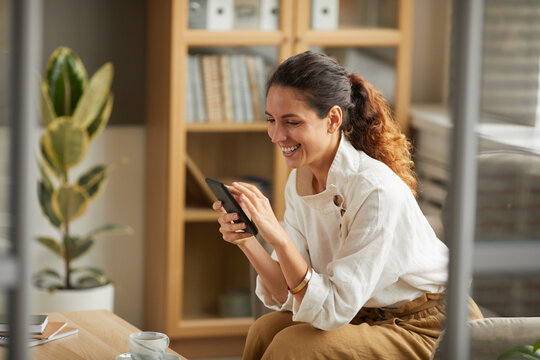 Portrait of elegant adult woman looking at smartphone screen and laughing while chatting online with friends and family, copy space