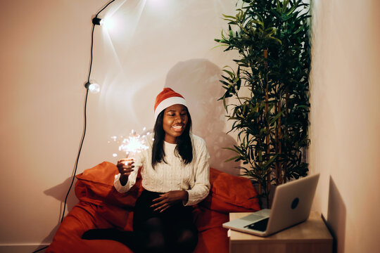 cheerful dark skin girl wearing santa claus hat and holding sparkler saying hello to friend and family during Christmas holiday using a laptop for video calling