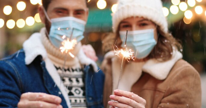 Close up of Caucasian happy couple holding sparklers while standing on decorated xmas street in medical masks in quarantine. Joyful man and woman celebrating new year 2021. Holiday celebration concept