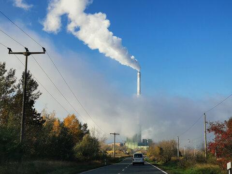 Große Fabrik mit Schornstein und viel Qualm vor blauem Himmel