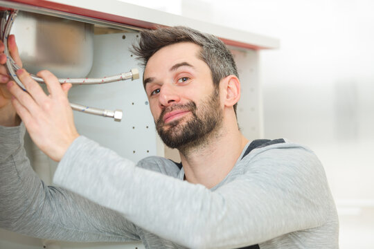 portrait of plumber fixing a sink