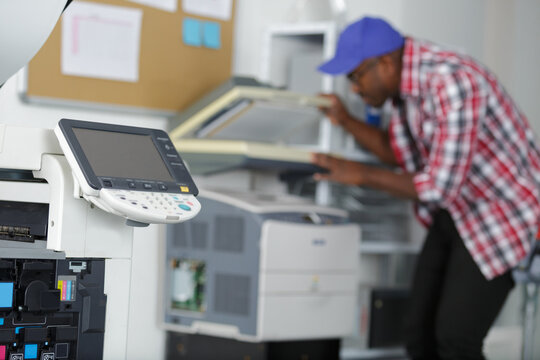 male technician repairing digital photocopier machine