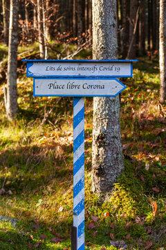Weiß-Blaues Hinweisschild in welche Richtung es gehen soll. Corona freier Platz oder Intensivbetten. Beschriftung in französischer Sprache