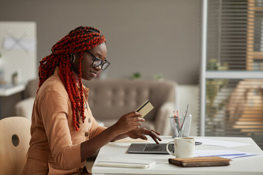 Side view portrait of young African-American woman holding credit card while enjoying online shopping at home office, copy space