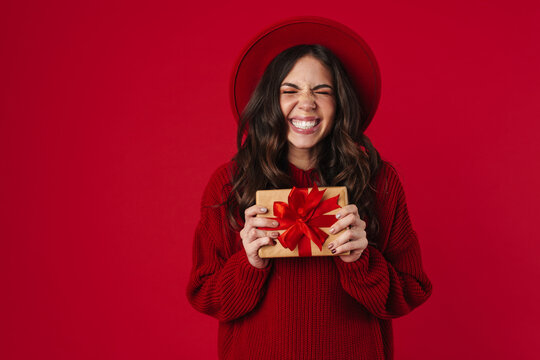Excited beautiful brunette girl in hat smiling and posing with gift box