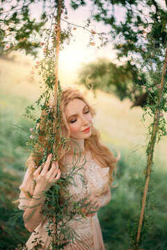 Young happy blonde woman in image of a forest nymph in a light peach vintage dress, stands near a tree. Fashion model girl posing on the background of summer green nature, sunset sun. Long blond hair.
