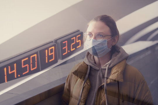A woman passenger in a medical mask stands at a digital display while waiting for a train to arrive, double exposure