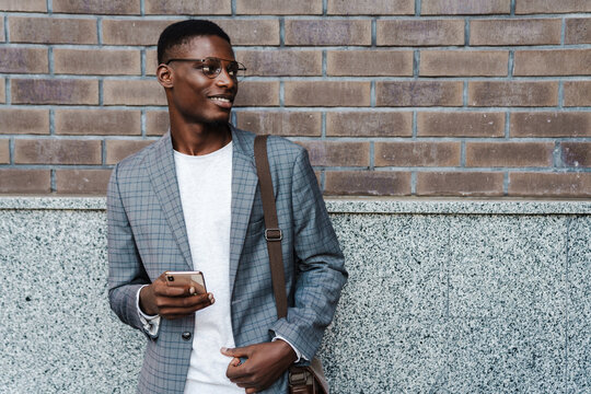 Happy african american man using mobile phone while standing