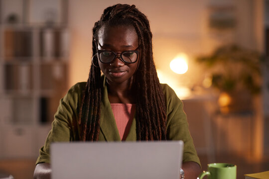 Front view portrait of young African-American woman using laptop while working in office or at home lit by cozy dim lighting, copy space