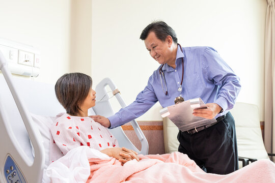 Asian doctor reassuring female patient sitting on hospital bed during consultation