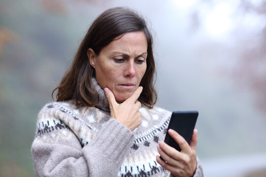 Worried middle age woman reading phone message in fall